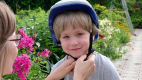 La mamá ayuda a su hijo puso un casco para montar con seguridad una bici en el parque de la ciudad almacen de video