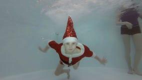 La mamá ayuda a un niño pequeño vestido como Santa Claus para zambullirse debajo del agua en la piscina del ` s de los niños Las
