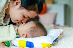 La mamá besa al hijo del bebé dormido fotografía de archivo