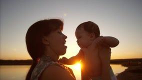 La mamá besa al pequeño bebé en el sol de oro de la tarde de la puesta del sol Cámara lenta metrajes