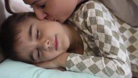 La mamá besa a su hijo querido mientras que él duerme en la cama y sonríe en su sueño HD almacen de video