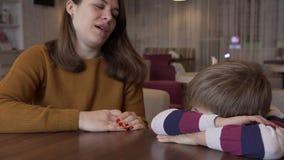 La mamá calma al pequeño hijo que fue ofendido por su sentada en una tabla en un café almacen de video