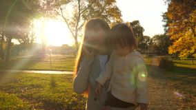 La mamá camina con el niño en sus brazos y negociaciones sobre un teléfono móvil La mamá con su hija en sus brazos está caminando metrajes
