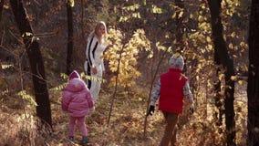 La mamá camina con la hija y el hijo en parque del otoño almacen de video