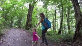 La mamá camina su mano de las hijas en el bosque Paseo de la familia en el bosque Viajes a la naturaleza Aire fresco y sano en almacen de metraje de vídeo