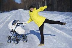 La mamá caucásica en capa amarilla está caminando con el carro de bebé blanco en el camino de la nieve entre el bosque en el día  Imagen de archivo libre de regalías