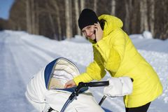 La mamá caucásica en capa amarilla está caminando con el carro de bebé blanco en el camino de la nieve entre el bosque en el día  Foto de archivo
