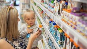 La mamá con el bebé busca productos del ` s del niño metrajes