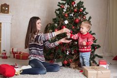 La mamá con el hijo adorna el árbol en la Navidad de los regalos del ` s del Año Nuevo Fotos de archivo