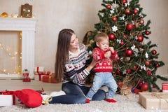 La mamá con el hijo adorna el árbol en la Navidad de los regalos del ` s del Año Nuevo Foto de archivo libre de regalías