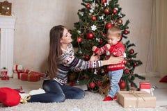 La mamá con el hijo adorna el árbol en la Navidad de los regalos del ` s del Año Nuevo Fotos de archivo libres de regalías