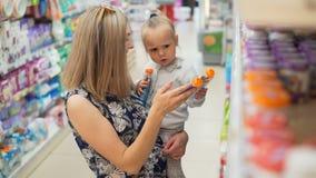 La mamá con el niño busca el puré y los jugos de la fruta del ` s del niño interiores metrajes