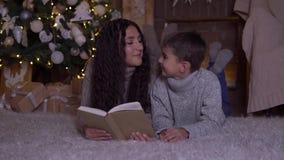 La mamá con el pelo largo lee un libro a su hijo y lo besa que miente en el piso cerca del árbol de navidad el día de la Navidad  almacen de video