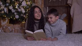 La mamá con el pelo largo lee un libro a su hijo y lo besa que miente en el piso cerca del árbol de navidad el día de la Navidad  almacen de metraje de vídeo
