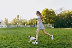 La mamá con la hija y los perros están caminando en el parque con un disco del vuelo fotos de archivo