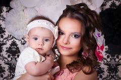La mamá con las flores en mi cabeza guarda al bebé 6 meses Foto de archivo libre de regalías
