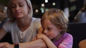 La mamá con los niños elige la pizza en un café y se divierte metrajes
