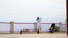 La mamá con un bebé en una silla de ruedas en la plataforma de observación toma imágenes de las hermosas vistas de la memoria del almacen de metraje de vídeo