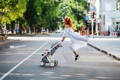 La mamá con un cochecito cruza el camino fotografía de archivo