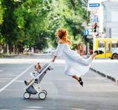 La mamá con un cochecito cruza el camino Imágenes de archivo libres de regalías