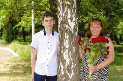La mamá con un ramo de flores rojas y un hijo se están colocando cerca de un árbol de abedul Foto de archivo