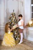 La mamá da a hija un regalo de la Navidad, árbol del nuevo-año fotografía de archivo libre de regalías