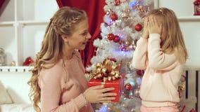 La mamá da un regalo a la hija cerca del árbol de navidad Fotos de archivo libres de regalías