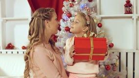 La mamá da un regalo a la hija cerca del árbol de navidad Imágenes de archivo libres de regalías