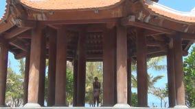 La mamá da vuelta en sus brazos a su pequeña hija en el edificio budista hermoso con las columnas almacen de metraje de vídeo
