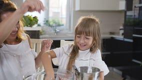 La mamá de dos muchachas con su niña en la cocina prepara la comida, un postre para la familia Como aprenden cocinarlos metrajes