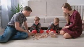 La mamá de la familia, el papá y dos hermanos gemelos juegan juntos la construcción fuera de bloques de madera en el piso almacen de video