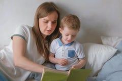 La mamá de la familia y el niño del hijo leyeron los libros que ponían en la cama Tiempo de la lectura de la familia foto de archivo