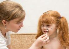 la mamá de la muchacha lubrica la curación para la varicela Imagen de archivo libre de regalías