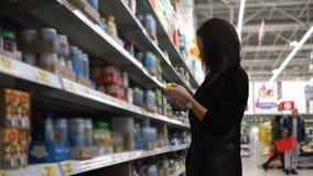La mamá de la mujer joven elige los alimentos para niños en la alameda para su bebé metrajes