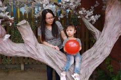 La mamá de la madre y de la hija y el pequeño bebé se divierten en muchacha del parque sentarse en un juego del árbol con mirada  Imagenes de archivo