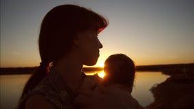 La mamá detiene al bebé en brazos del sol en la puesta del sol Cámara lenta metrajes