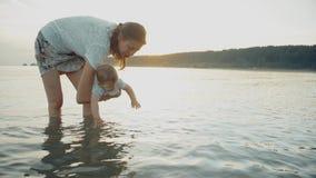La mamá detiene al bebé en sus brazos, el bebé alcanza para el agua y la salpica almacen de video