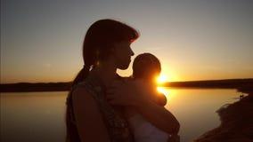 La mamá detiene al niño en brazos del sol en la puesta del sol Cámara lenta almacen de video