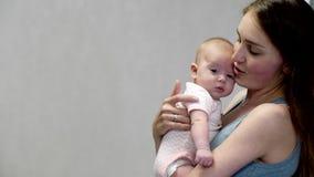 La mamá detiene a una pequeña hija alegre en sus brazos