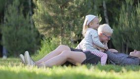 La mamá, el hijo y la pequeña hija están jugando con un papel de piedra de las tijeras en el par