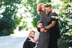 La mamá, el papá, el pequeño hijo y la hija se divierten fotografía de archivo