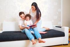La mamá, el papá y el bebé leyeron un libro en el sofá en el cuarto padres Foto de archivo libre de regalías
