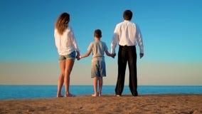 La mamá, el papá y el hijo se están colocando en la playa y están mirando en la distancia metrajes