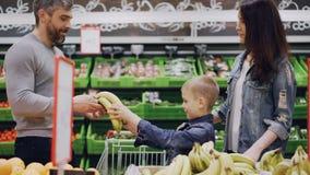La mamá, el papá y el muchacho lindo están eligiendo la fruta en tienda de alimentación, el niño está oliendo plátanos y dándolos metrajes