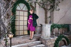La mamá embarazada linda se coloca en la terraza adornada hermosa de la Navidad, tiempo feliz del embarazo Foto de archivo libre de regalías