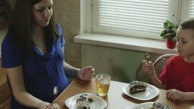 La mamá embarazada y el pequeño hijo están comiendo la tortade y el té de consumición en la tabla de cocina almacen de metraje de vídeo