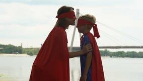 La mamá en traje del super héroe besa la frente del hijo, abrazando, ayuda en principios almacen de metraje de vídeo