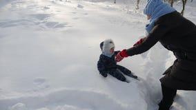 La mamá en una chaqueta negra lanza a un pequeño hijo en la nieve en el invierno metrajes