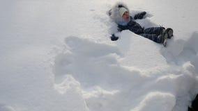 La mamá en una chaqueta negra lanza a un pequeño hijo en la nieve en el invierno almacen de metraje de vídeo