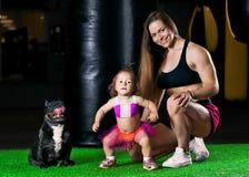 La mamá encantadora de los deportes entrena en el gimnasio con su pequeña hija a fotografía de archivo libre de regalías